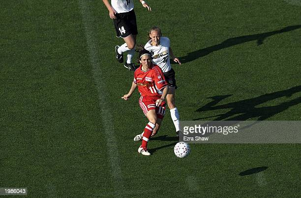 Forward Marinette Pichon of the Philadelphia Charge moves the ball against midfielder Krista Davey of the New York Power during the WUSA match at...