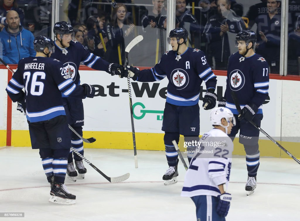 Forward Mark Scheifele #55 of the Winnipeg Jets celebrates his goal with teammates forward Blake Wheeler #26, forward Patrik Laine #29 and forward Adam Lowry #17 during NHL action against the Toronto Maple Leafs during NHL action on October 4, 2017 at the Bell MTS Place in Winnipeg, Manitoba.