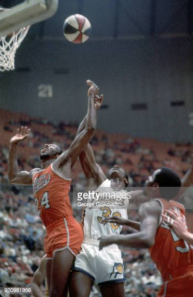 Forward Marvin Barnes of the Spirits of St Louis battles forward George McGinnis of the Indiana Pacers for the ball as Goo Kennedy of the Spirits...