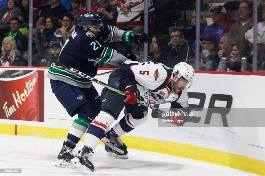 Forward Matthew Wedman #21 of the Seattle Thunderbirds delivers a hit against defenceman Austin McEneny #5 of the Windsor Spitfires on May 21, 2017 during Game 3 of the Mastercard Memorial Cup at the WFCU Centre in Windsor, Ontario, Canada.