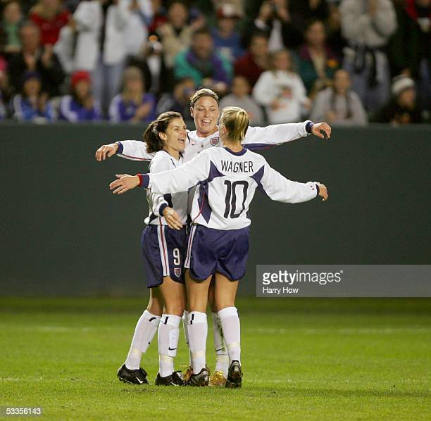 """Forward Mia Hamm of the USA celebrates with her teammates, forward Abby Wambach and midfielder Aly Wagner, during the """"Fan Celebration Tour"""" finale..."""