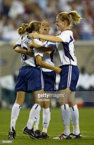 Forward Mia Hamm of the USA is greeted by her teammates midfielder Julie Foudy and forward Cindy Parlow after scoring a penalty kick goal gainst...