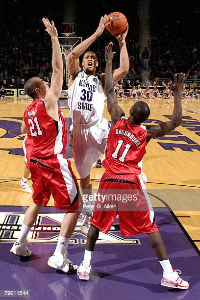 Forward Michael Beasley of the Kansas State Wildcats drives the lane against pressure from Nebraska Cornhuskers center Aleks Maric and guard Ade...