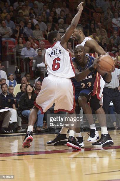 Forward Michael Jordan of the Washington Wizards passes around guard Eddie Jones of the Miami Heat during the NBA game at American Airlines Arena in...