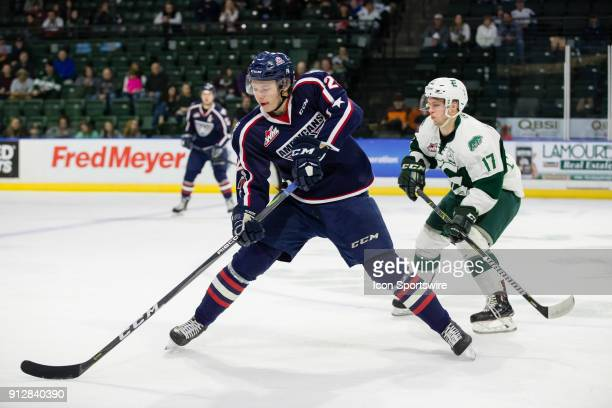 Forward Morgan Geekie of the TriCity Americans dumps the puck into the zone on his backhand away from Everett Silvertips forward Matt Fonteyne during...
