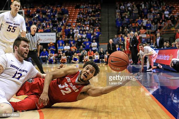 Forward Nick Duncan of the Boise State Broncos and forward Tim Williams of the New Mexico Lobos dive for a loose ball during second half action on...