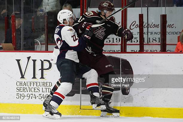 Forward Nick Isaacson of the Peterborough Petes is checked into the boards by forward Cole Caarter of the Windsor Spitfires on November 13 2016 at...