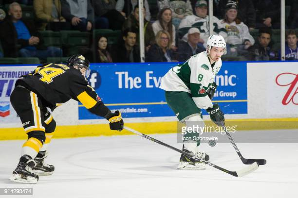 Forward Patrick Bajkov of the Everett Silvertips flips a backhand pass over the stick of Brandon Wheat Kings forward Ty Lewis during the first period...