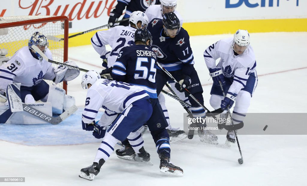 Forward Patrick Marleau #12 of the Toronto Maple Leafs clears the puck from Winnipeg Jets players during NHL action on October 4, 2017 at the Bell MTS Place in Winnipeg, Manitoba.
