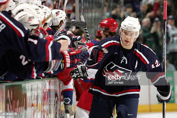 Forward Patrick O'Sullivan is congratulated by teammates after scoring against Russia during the semifinal game of the World Junior Hockey...