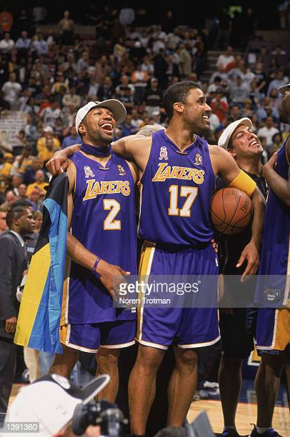 Forward Rick Fox of the Los Angeles Lakers throws his arm around point guard Derek Fisher after winning Game Four of the 2002 NBA Finals against the...