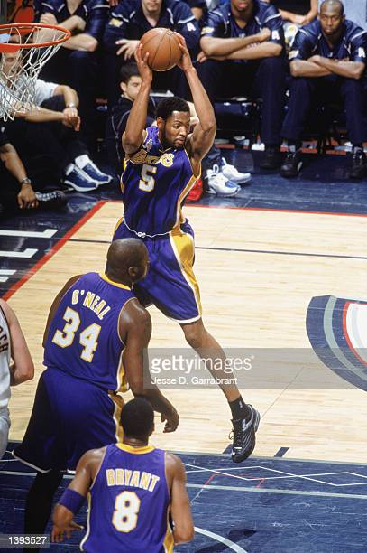 Forward Robert Horry of the Los Angeles Lakers hauls in a rebound over center Shaquille O'Neal and guard Kobe Bryant during Game Four of the 2002 NBA...