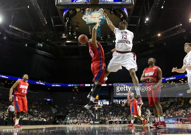 Forward Ronald Roberts of the Saint Joseph's Hawks dunks the ball over forward Jalen Robinson of the Dayton Flyers in the Quarterfinals of the men's...