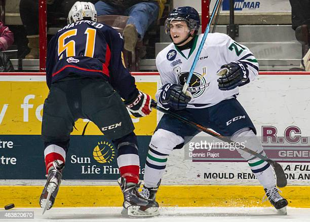 Forward Ryan Moore of the Plymouth Whalers battles for the puck against defenceman Jalen Chatfield of the Windsor Spitfires on February 18 2015 at...