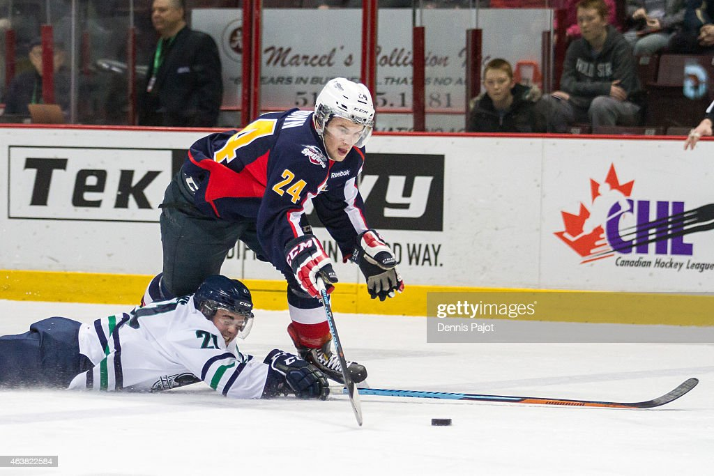 Forward Ryan Moore #21 of the Plymouth Whalers battles for the puck against defenceman Graeme Brown #24 of the Windsor Spitfires on February 18, 2015 at the WFCU Centre in Windsor, Ontario, Canada.