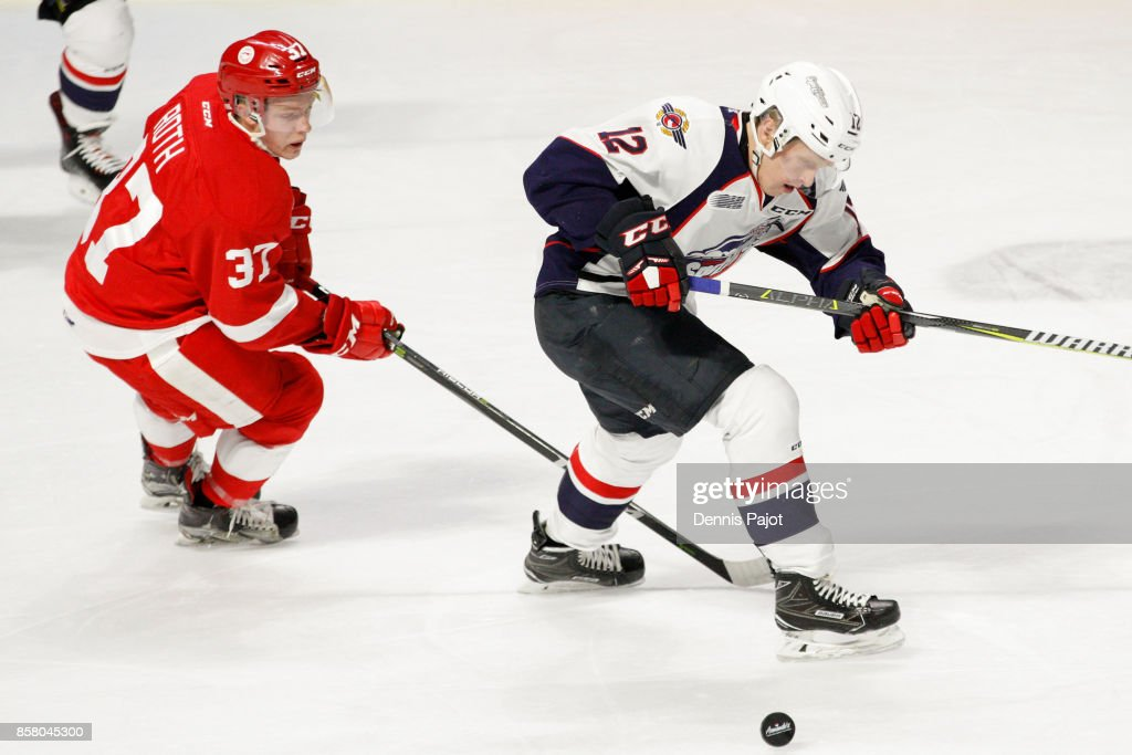 Forward Ryan Roth #37 of the Sault Ste. Marie Greyhounds battles for the puck against forward William Sirman #12 of the Windsor Spitfires on October 5, 2017 at the WFCU Centre in Windsor, Ontario, Canada.