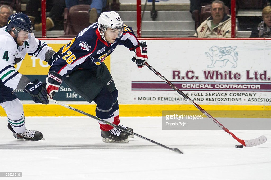 Forward Sam Povorozniouk #26 of the Windsor Spitfires moves the puck against defenceman Sean Callaghan #4 of the Plymouth Whalers on February 18, 2015 at the WFCU Centre in Windsor, Ontario, Canada.