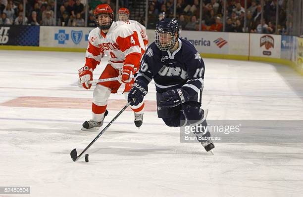 Forward Sean Collins of the New Hampshire Wildcats moves the puck ahead of defenseman Sean Sullivan of the Boston University Terriers on March 18,...