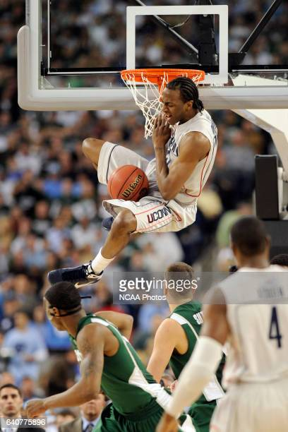 Forward Stanley Robsinson of the University of Connecticut hangs onto the net after a big slam dunk during the semifinal game of the 2009 Men's Final...