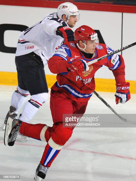 US forward Stephen Gionta and Russia's defender Yevgeny Medvedev vie for the puck during a preliminary round game Russia vs USA of the IIHF...