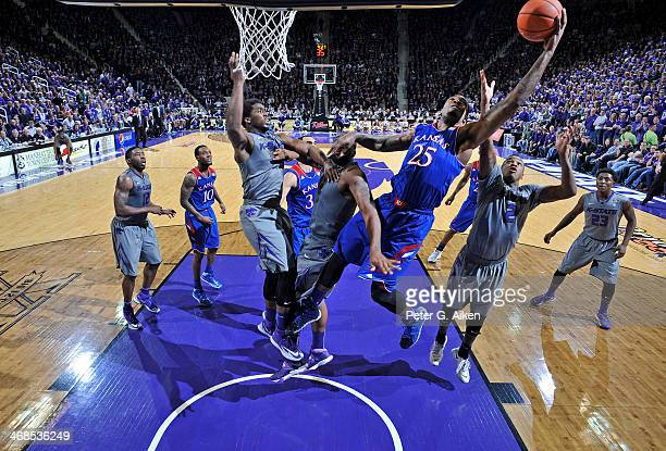 Forward Tarik Black of the Kansas Jayhawks reaches for a ball over guard Marcus Foster of the Kansas State Wildcats during the second half on...