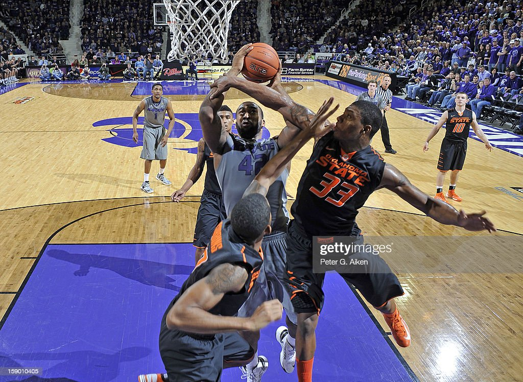 Forward Thomas Gipson #42 of the Kansas State Wildcats drives to the basket against guard Marcus Smart #33 of the Oklahoma State Cowboys during the first half on January 5, 2013 at Bramlage Coliseum in Manhattan, Kansas. Kansas State defeated Oklahoma State 73-67.