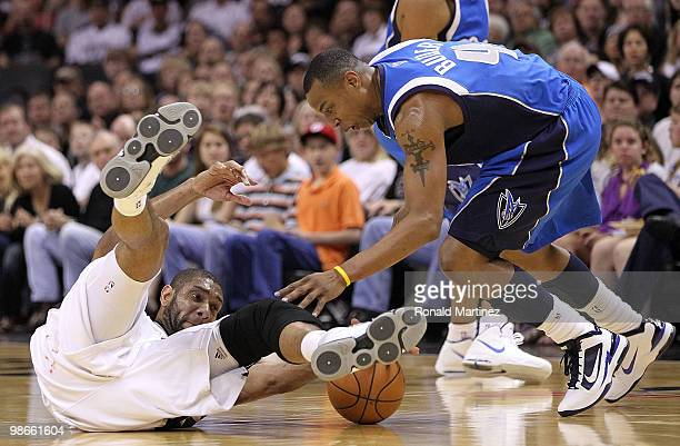 Forward Tim Duncan of the San Antonio Spurs falls with the ball against Caron Butler of the Dallas Mavericks in Game Four of the Western Conference...