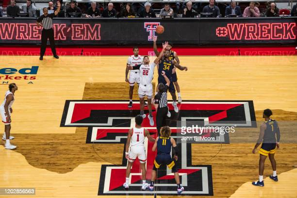Forward TJ Holyfield of the Texas Tech Red Raiders battles for the jump ball against forward Oscar Tshiebwe of the West Virginia Mountaineers during...