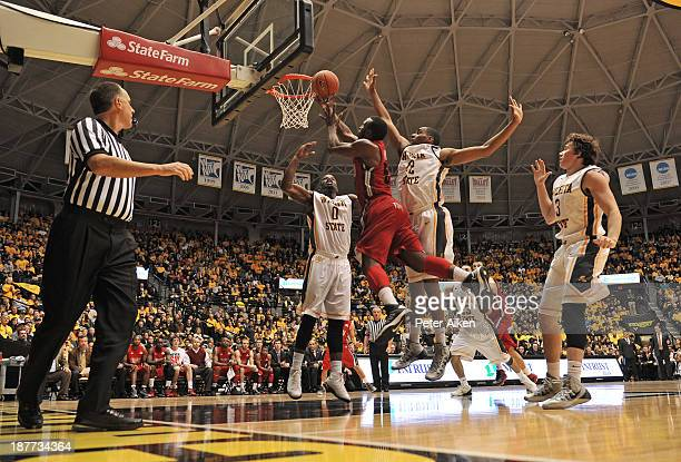 Forward TJ Price of the Western Kentucky Hilltoppers drive to the basket between defenders Chadrack Lufile and Darius Carter of the Wichita State...