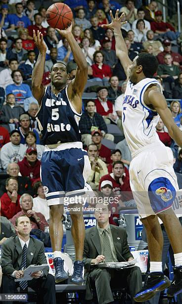 Forward Toraino Johnson of the Utah State Aggies takes a jumpshot over Keith Langford of the Kansas Jayhawks during the first round of the NCAA...