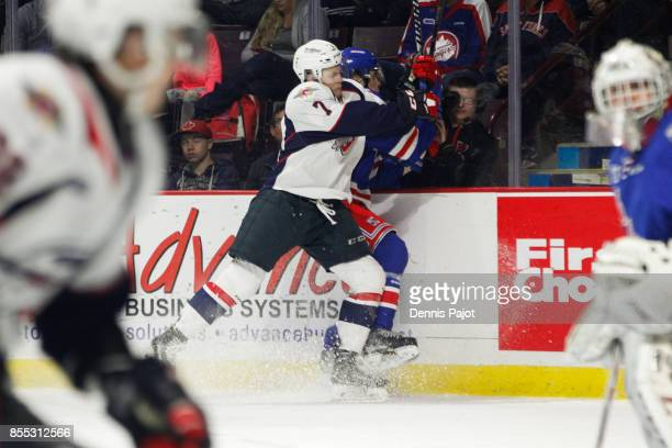 Forward Tyler Angle of the Windsor Spitfires places a hit against forward Rickard Hugg of the Kitchener Rangers on September 28 2017 at the WFCU...