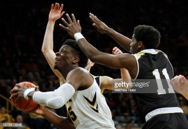 Forward Tyler Cook of the Iowa Hawkeyes drives to the basket in the second half between guards Adam Grant and Tanner Johnson of the Bryant Bulldogs...