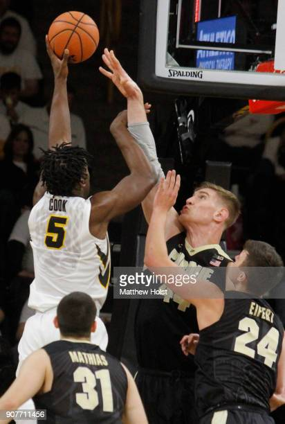 Forward Tyler Cook of the Iowa Hawkeyes goes to the basket in the second half in front of center Issac Haas and guard Grady Eifert of the Purdue...