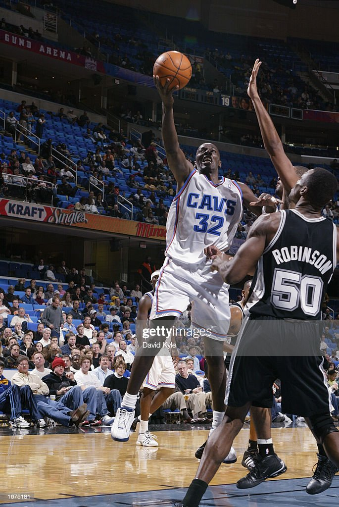 Forward Tyrone Hill #32 of the Cleveland Cavaliers shoots a layup past center David Robinson #50 of the San Antonio Spurs during the game at Gund Arena on November 16, 2002 in Cleveland, Ohio. The Spurs won 90-77.