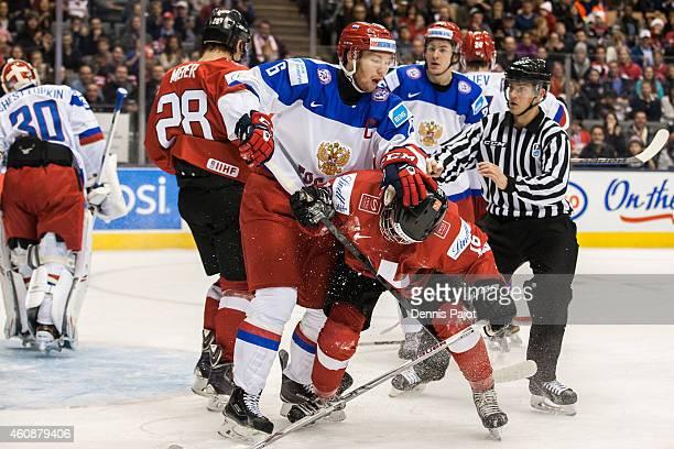 Forward Vladislav Gavrikov of Russia battles in front of the net with Denis Malgin of Switzerland during the 2015 IIHF World Junior Championship on...