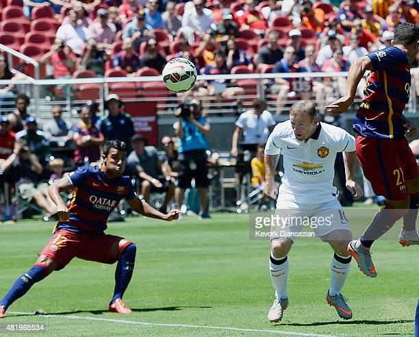Forward Wayne Rooney of Manchester United scores a goal as Rafinha of FC Barcelona looks on during the first half of the International Champions Cup...