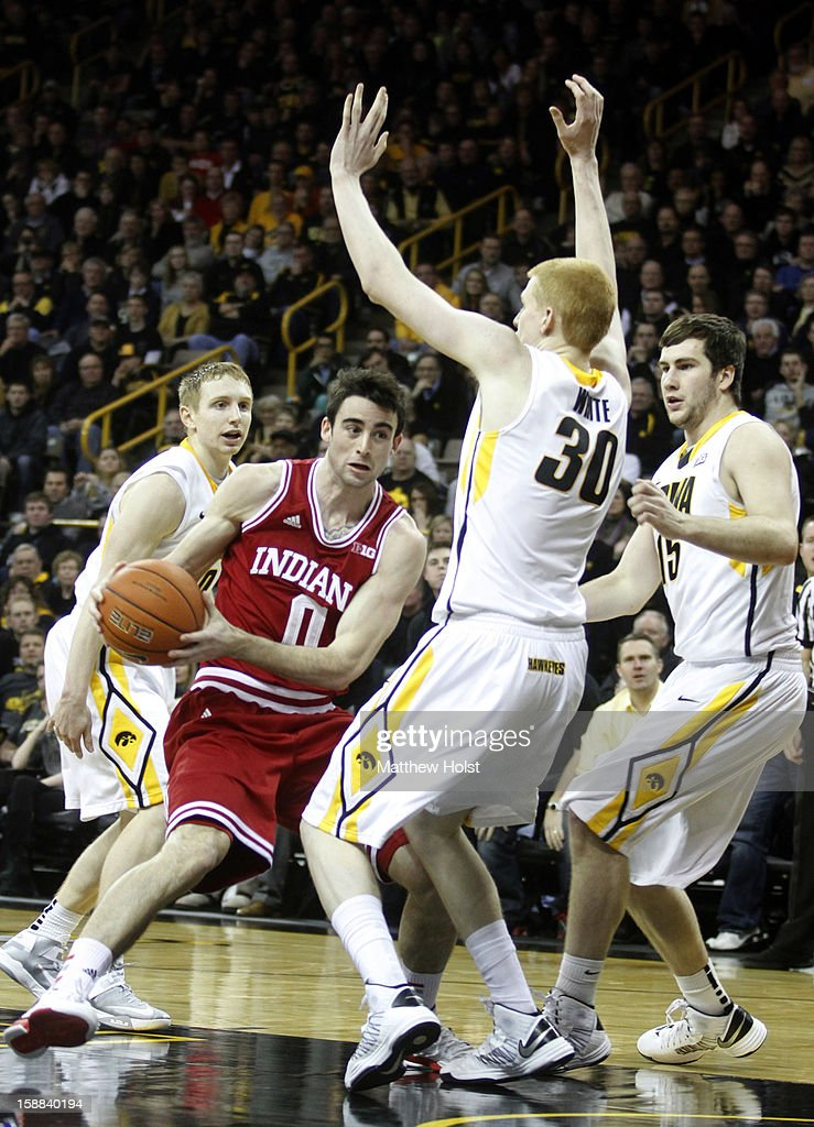 Forward Will Sheehery #0 of the Indiana Hoosiers drives down the court during the second half against guard Mike Gesell #10 and forwards Aaron White #30 and Zach McCabe #15 on December 31, 2012 at Carver-Hawkeye Arena in Iowa City, Iowa. Indiana won 69-65.