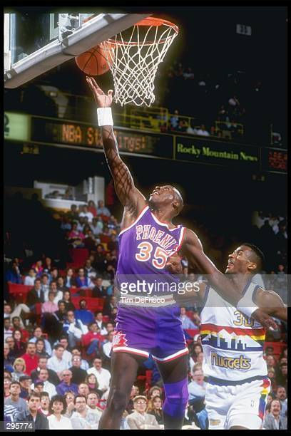 Forward Xavier McDaniel of the Phoenix Suns lays up the ball during a game against the Denver Nuggets at the McNichols Arena in Denver Colorado...