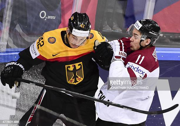 Forward Yasin Ehliz of Germany and defender Kristaps Sotnieks of Latvia vie for the puck during the group A preliminary round match Germany vs Latvia...