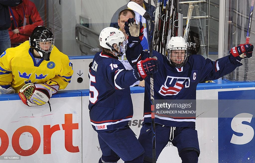US forwards J T Compher (R) and John Hayden (C) celebrate their 4-0 victory over team Sweden as Swedish goalkeeper Jonas Johanso (L) looks on on April 25, 2013 during a quarter-final game of the IIHF U18 International Ice Hockey World Championship in Sochi.