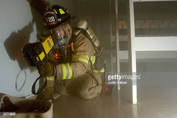 Foster City firefighter Larry Moore makes his way through a dark smoke filled room with a thermal imaging camera during a multiagency drill December...