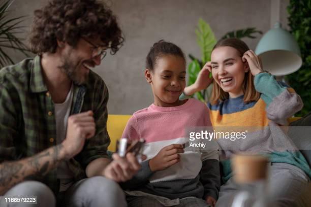 pleegvader geeft chocolade aan zijn pleeg dochter - adoptie stockfoto's en -beelden