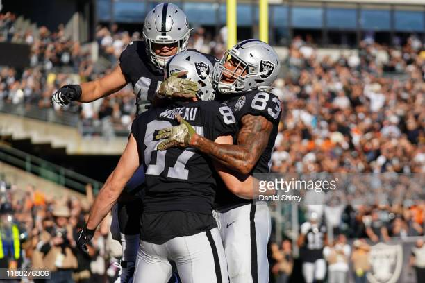Foster Moreau celebrates catching a touchdown pass with Darren Waller of the Oakland Raiders during the first half against the Cincinnati Bengals at...