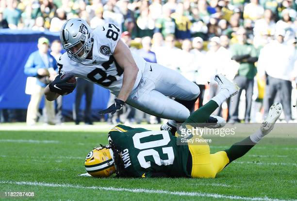Foster Moreau of the Oakland Raiders scores a touchdown over Kevin King of the Green Bay Packers during the second quarter in the game at Lambeau...
