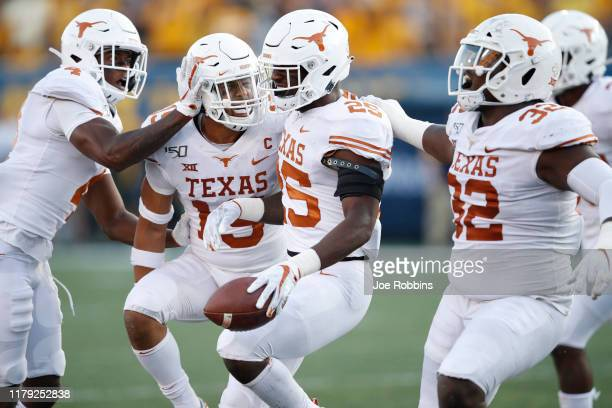 J Foster of the Texas Longhorns celebrates with teammates after intercepting a pass in the second half against the West Virginia Mountaineers at...