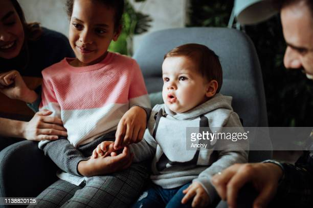 Foster parents watching TV with their kids