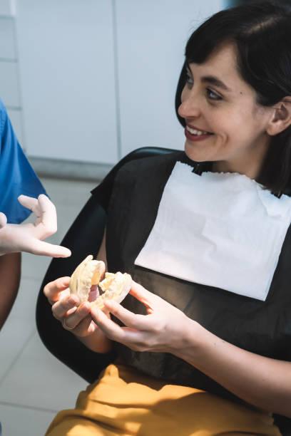 Foto vertical de una mujer joven en la consulta del dentista. La paciente sostiene un yeso dental en sus manos mientras mira a su dentista sonriendo.