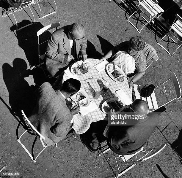 Foto von oben auf vier Personen die an einem Tisch im Freien essen um 1950Aufnahme Fritz Eschen