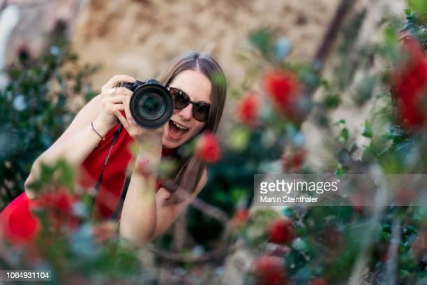 fotografin in rotem kleid mit kamera in der hand - kleid stock pictures, royalty-free photos & images