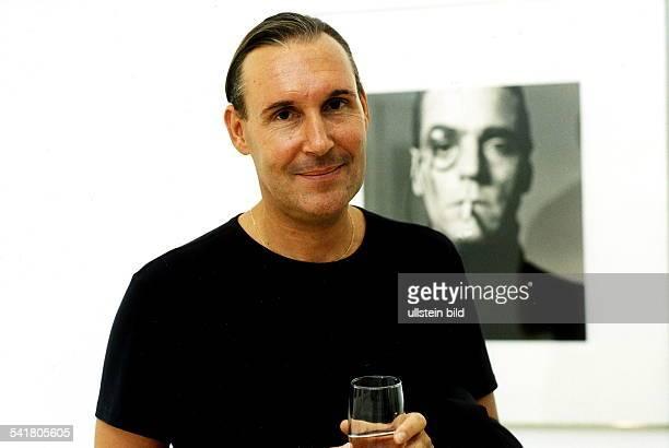 FotografPorträt steht mit einem Glas in der Handvor einem seiner Fotos September 1999